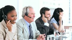 Serious call centre agents talking with headsets Stock Footage