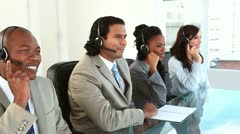 Happy call centre agents working with headsets - stock footage