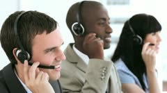 Smiling call centre agent working with his colleagues - stock footage