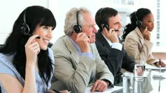 Happy brunette call centre agent working with her colleagues - stock footage