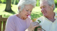 Retired woman smelling a rose with her husband Stock Footage