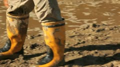 Child walking in mud with gumboots. Stock Footage