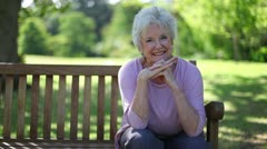 Retired woman smiling while sitting on a bench Stock Footage