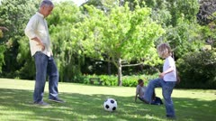Father playing football with his children Stock Footage
