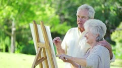 Retired woman showing something to her husband Stock Footage