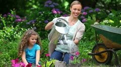 Mother watering flowers while her daughter is watching Stock Footage