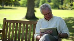 Retired man using an ebook Stock Footage