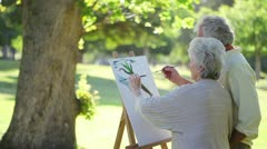 Retired people painting a tree together Stock Footage