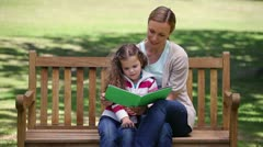 Mother and daughter looking a picture book together Stock Footage
