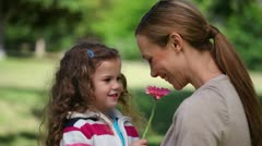 Mother smelling a flower holding by her daughter Stock Footage