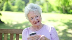 Retired woman using a mobile phone Stock Footage