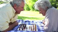 Two retired people playing chess Stock Footage