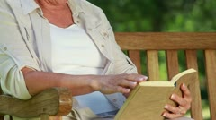 Happy mature woman reading a novel Stock Footage