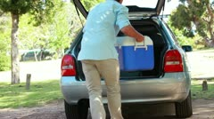 Rear view of a man placing his cooler in his car Stock Footage