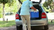 Stock Video Footage of Rear view of a man placing his cooler in his car