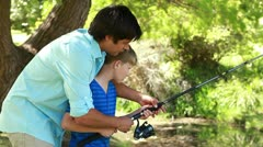 Father and son using a fishing rod together Stock Footage