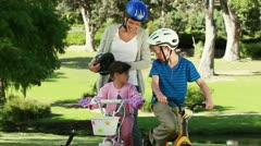 Smiling mother fastening the helmets of her children - stock footage