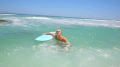 Blonde man holding a blue surfboard Stock Footage