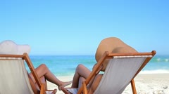 Peaceful woman resting while sitting on deck chairs Stock Footage