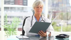 Mature practitioner holding documents Stock Footage