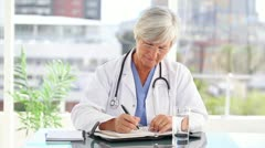 Serious mature doctor writing on her calendar - stock footage