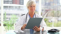 Smiling mature doctor looking at files Stock Footage