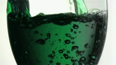 Green trickle in a super slow motion filling a tumbler glass - stock footage