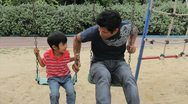 Stock Video Footage of Asian Father And Son Playing On Swings At Playground