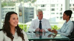 Portrait of a businesswoman with co-workers in background - stock footage