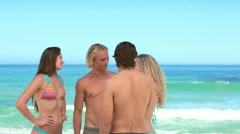 Friends chatting to each other at the beach Stock Footage