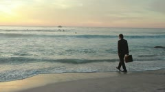Well dressed businessman walks into the ocean Stock Footage