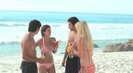 Stock Video Footage of Four attractive people standing with cocktails at the beach