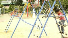 Boy climbing up a rope ladder in a playground Stock Footage