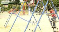 Stock Video Footage of Boy climbing up a rope ladder in a playground
