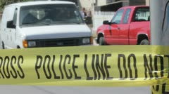 Crime scene coroners van leaving with police tape in the foreground Stock Footage