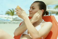 Woman sitting on the beach and putting make up NTSC Stock Footage