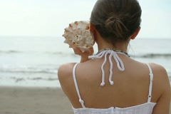 Portrait of young woman with seashell on the beach NTSC Stock Footage