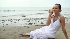 Young woman with seashell sitting on the beach HD Stock Footage