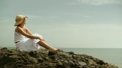 Young woman sitting on the stone by the sea HD Stock Footage