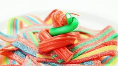 Colorful gummy candy rotating on a white plate - stock footage