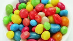 Multicolor bonbon sweets (ball candies) rotating on white plate Stock Footage