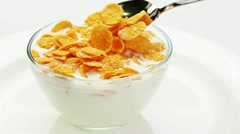 Cooking corn flakes with milk in a glass bowl stirring by spoon Stock Footage