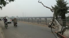 Donkey- and horse carts on a bridge in Lahore Stock Footage