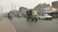 View of the roadside in Lahore Pakistan as busy traffic drives by Stock Footage
