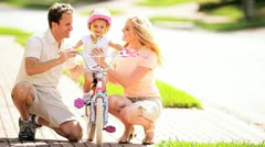 Young Parents Supporting Toddler on Little Bicycle Stock Footage