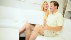 Young Heterosexual Couple Using Laptop Home - stock footage