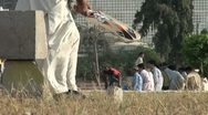 A man waits to bat in a park in Karachi Stock Footage