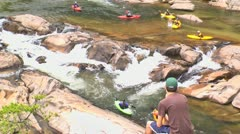 Young man watches kayakers on river rapids Stock Footage