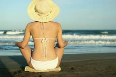 Sexy woman in summer hat and bikini sitting on the beach NTSC Stock Footage