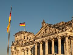 German flag flying over reichstag bundestag Stock Photos